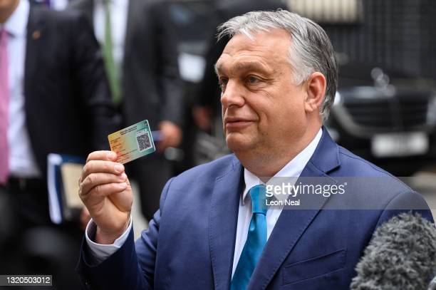 Hungarian Prime Minister Viktor Orbán holds up his COVID-19 vaccination card after a meeting with UK Prime Minister Boris Johnson at Downing Street...