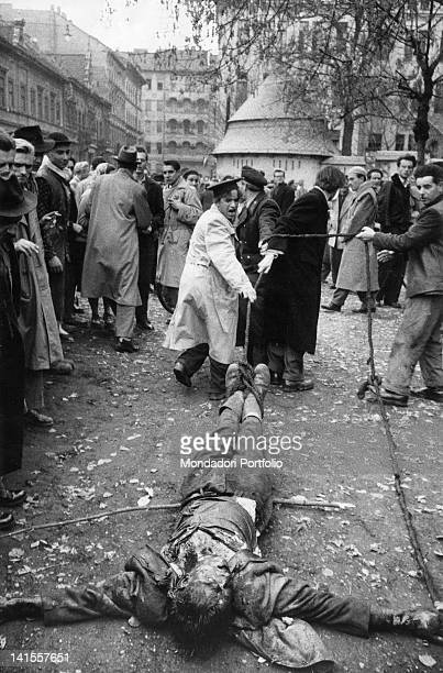 Hungarian rebels dragging the corpse of an AVH colonel by the feet to hang him Budapest November 1956