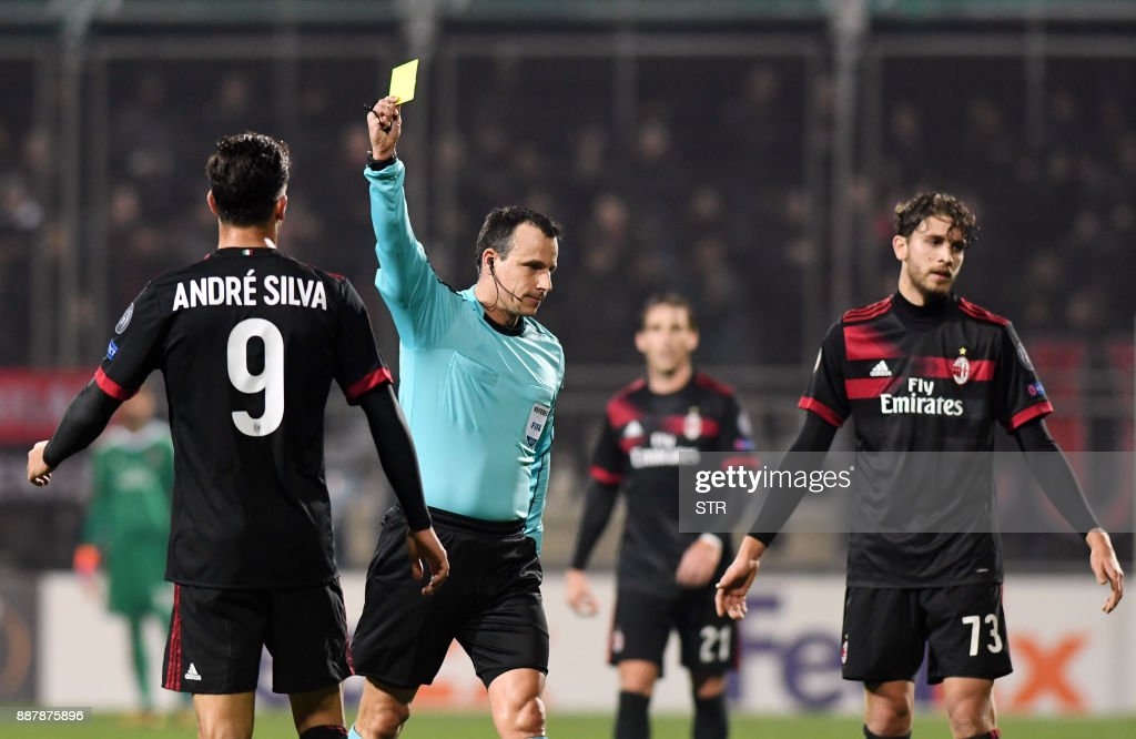 Hungarian referee Istvan Vad (C) shows a yellow card to AC Milan's forward Andre Silva (L) during the UEFA Europa League Group D football match between HNK Rijeka and AC Milan at The Rujevica Stadium in Rijeka on December 7, 2017. /