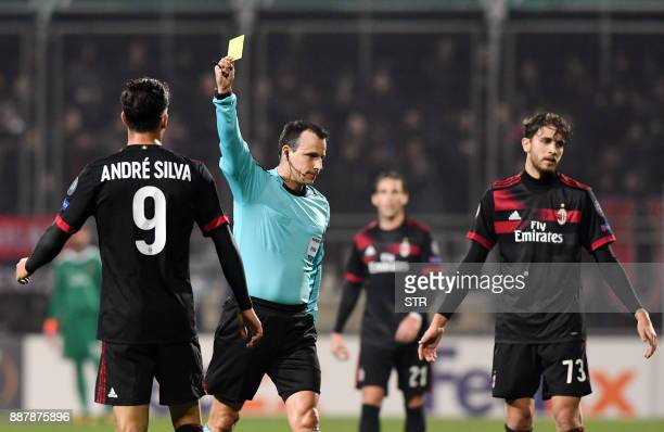 Hungarian referee Istvan Vad shows a yellow card to AC Milan's forward Andre Silva during the UEFA Europa League Group D football match between HNK...