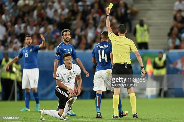 Hungarian referee Viktor Kassai gives a yellow card to Italy's midfielder Stefano Sturaro as teamates midfielder Marco Parolo and defender Andrea...
