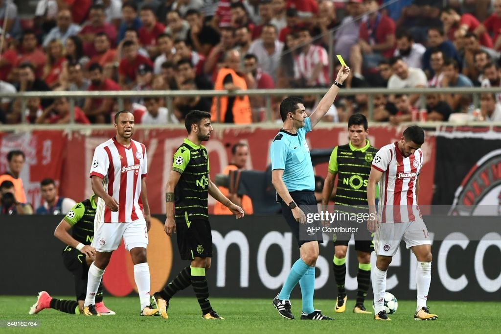 Hungarian referee Viktor Kassai (C) gives a yellow card to Olympiacos' Norwegian Defender Omar Elabdellaoui (R) during the UEFA Champions League Group D football match between Olympiacos Piraeus FC and Sporting Lisbon on September 12, 2017 at the Karaiskaki stadium in Athens. /