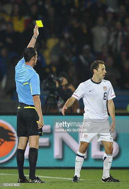 Hungarian referee Viktor Kassai hands a yellow card to US defender Steve Cherundolo during the 2010 World Cup round of 16 football match USA vs Ghana...