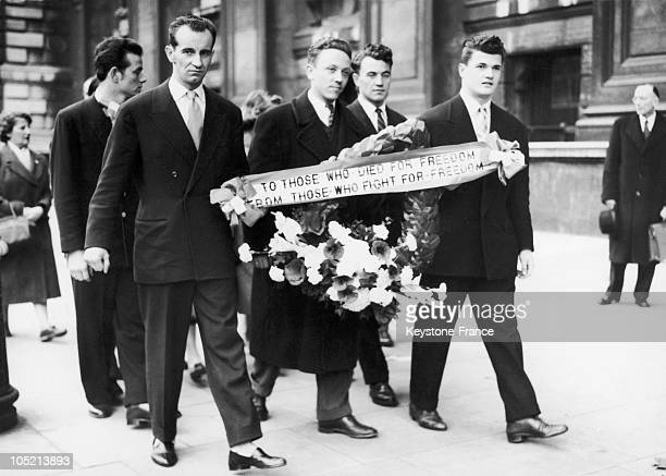 Hungarian Refugees Carrying A Wreath Of Flowers To A Cenotaph To Celebrate The First Anniversary Of The Hungarian Insurrection Of November 1956...