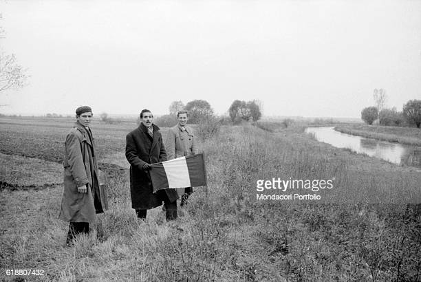 Hungarian revolution of 1956. Three Hungarian refugees posing with the Hungarian flag at the border between Austria and Hungary. November 1956