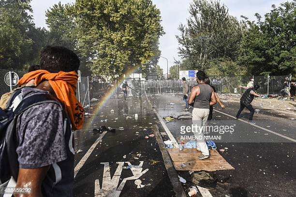 Hungarian riot police uses water canon and pepper spray to disperse refugees at the Hungarian border with Serbia near the town of Horgos on September...