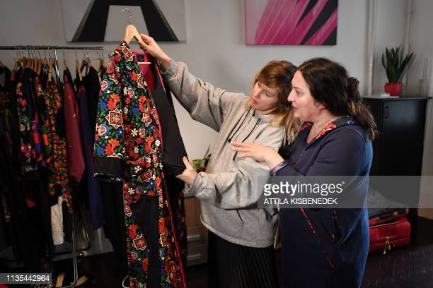Hungarian Roma fashion designer and founder of Romani Design Erika Varga talks with a model before a video and photo shooting for a campaign to...