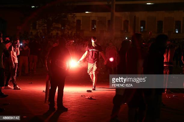 A Hungarian soccer fan throws a firework rocket during clashes with riot police after a Euro 2016 qualifying football match between Hungary and...