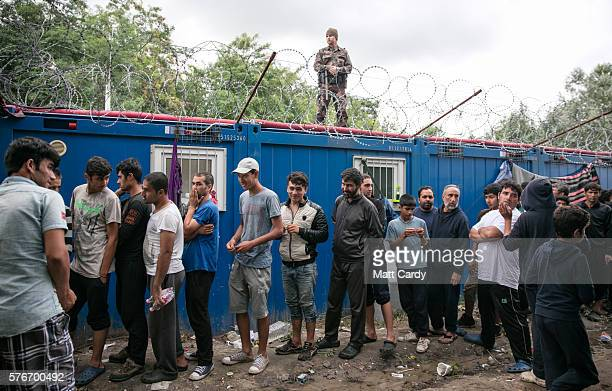 Hungarian soldier looks down on migrants queueing for food being distributed from a doorway in the border fence close to the E75 Horgas border...