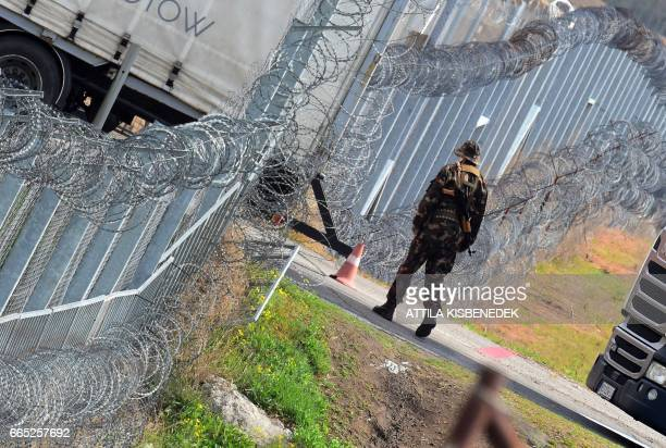 A Hungarian soldier patrols at the Hungarian border fence at the Tompa border station transit zone on April 6 2017 as the Hungarian Interior Minister...