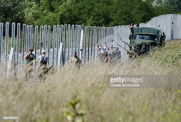 Hungarian soldiers and other officials prepare the next part of a border fence near the border village Morahalom at the HungarianSerbian border on...