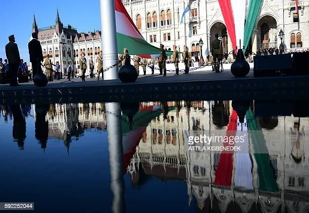 Hungarian soldiers stand guard with the Hungarian national flag as new officers of the Hungarian Army take their military oath in front of the...