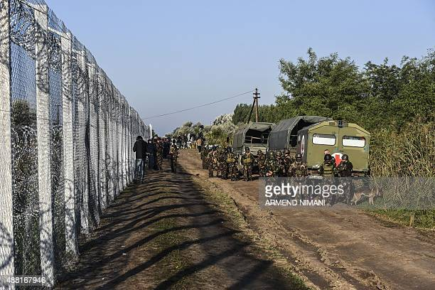 Hungarian soldiers stand in front of a fence at the Hungarian border with Serbia near the town of Horgos on September 14 2015 A record 5809 migrants...