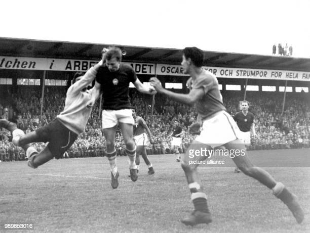 Hungarian striker Laszlo Budai fails to reach the ball Mexican goalkeeper Antonio Carbajal clears with his fist in front of Mexican defender Carlos...
