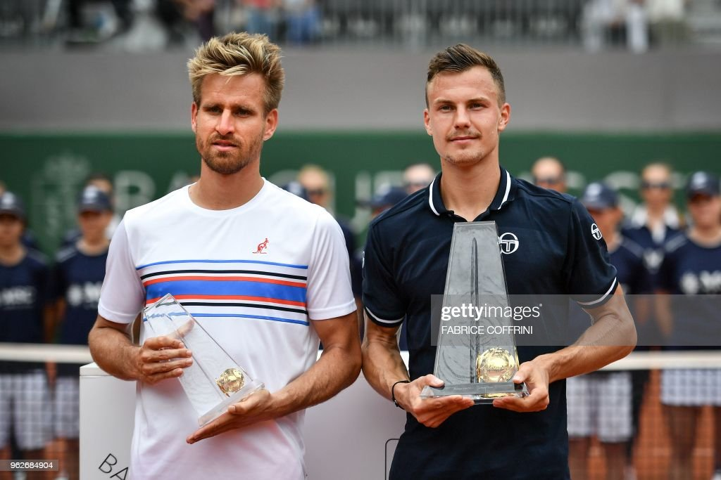 Hungarian tennis player Marton Fucsovics (R) poses with German tennis player Peter Gojowczyk after winning the final game at the Geneva Open ATP 250 tennis tournament, in Geneva on May 26, 2018.