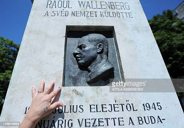 A Hungarian woman touches the memorial stone of late Swedish diplomat Raoul Wallenberg in St Istvan park of Budapest on August 1 2012 prior to the...