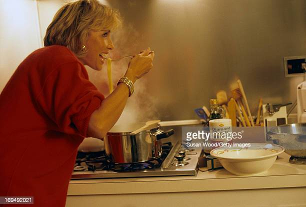 Hungarianborn American fashion designer Adrienne Vittadini eats spaghetti from steaming pot on the stove in her kitchen New York New York October 1984