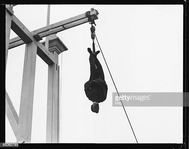 Hungarianborn American magician escape artist and psychic debunker Harry Houdini wears a straitjacket and hangs from a beam as he performs one of his...