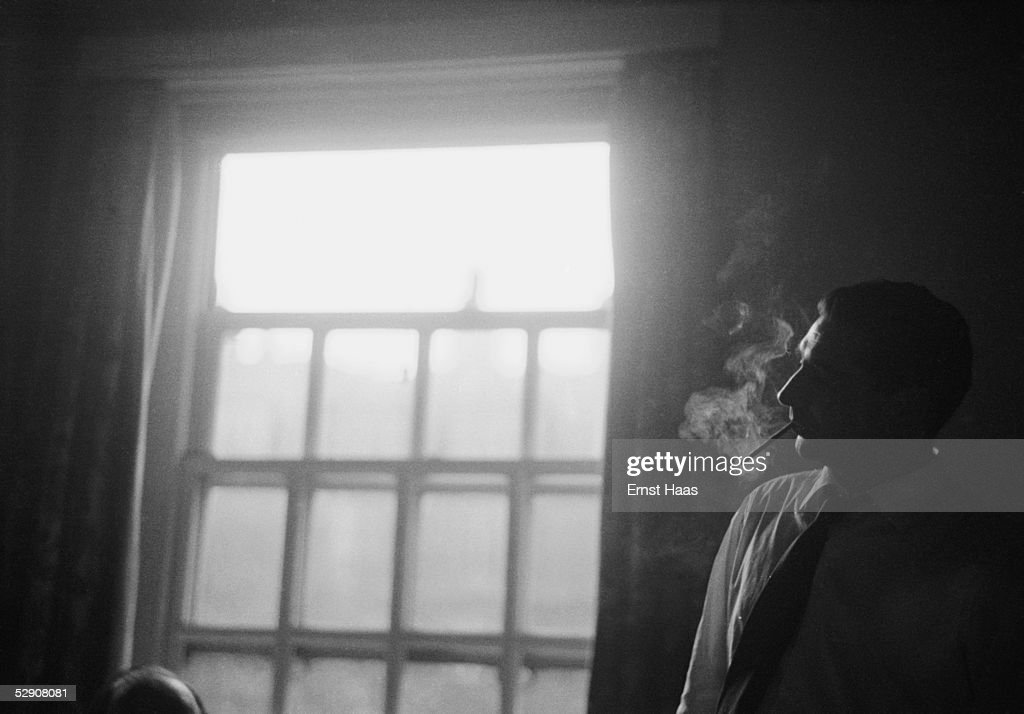 Hungarian-born American photojournalist Robert Capa (1913 - 1954), during a visit to film director John Huston in hospital, 1953.