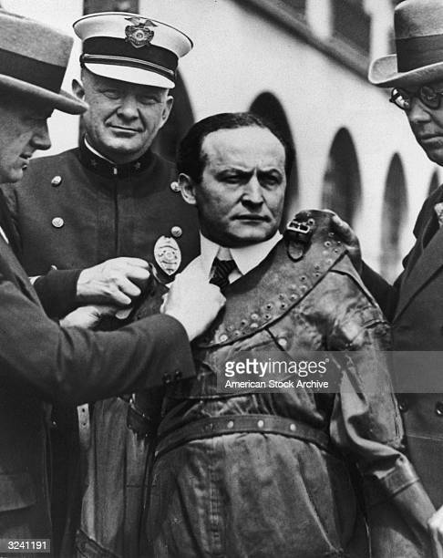Hungarianborn magician Harry Houdini aka Ehrich Weiss is strapped into a leather straight jacket by three men