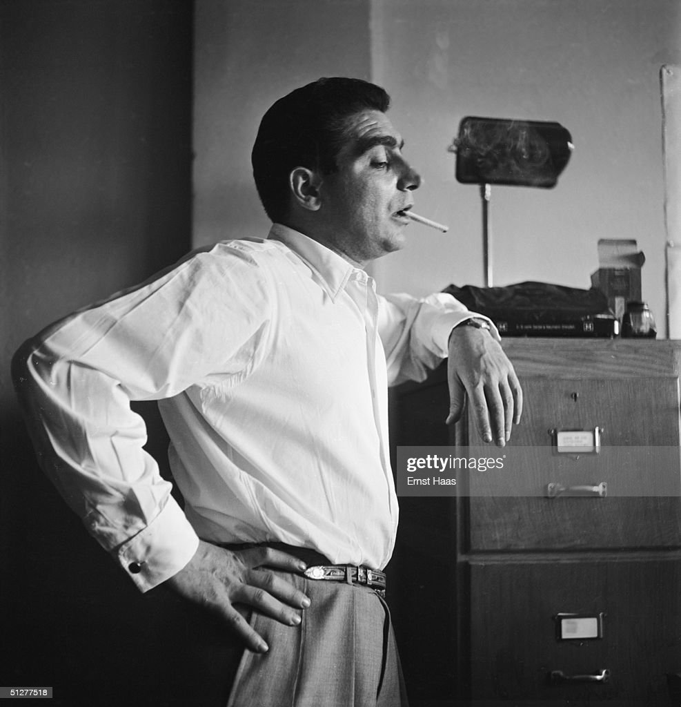 Hungarian-born photojournalist Robert Capa (1913 - 1954) at a meeting of the Magnum photographic co-operative, Paris, circa 1947.