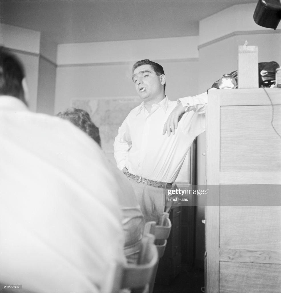Hungarian-born photojournalist Robert Capa (1913 - 1954) at a meeting of the Magnum photographic co-operative, Paris, circa 1947.
