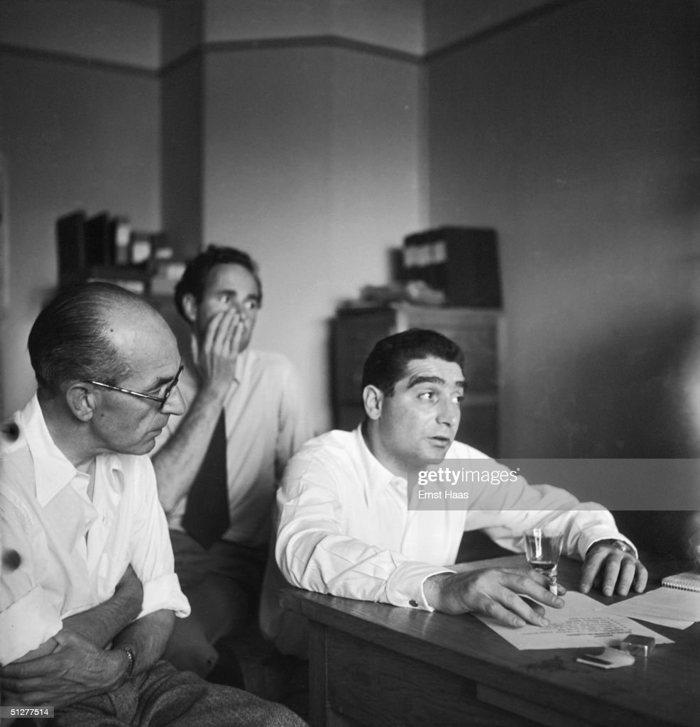 Hungarian-born photojournalist Robert Capa (1913 - 1954) chairs a meeting of the Magnum photographic co-operative, Paris, circa 1947. Swiss photographer Werner Bischof (1916 - 1954), can be seen in the background, centre.