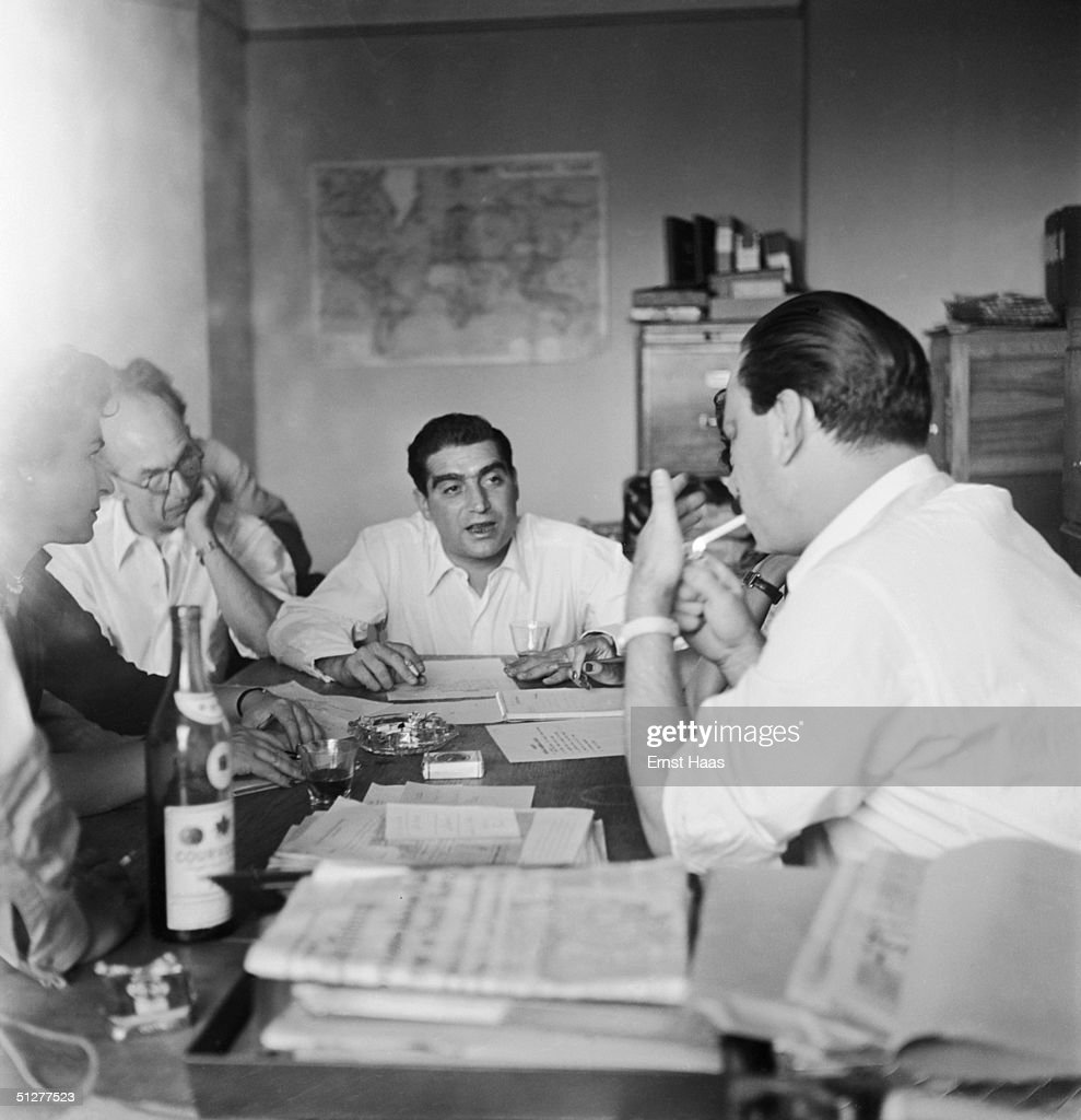 Hungarian-born photojournalist Robert Capa (1913 - 1954) chairs a meeting of the Magnum photographic co-operative, Paris, circa 1947.