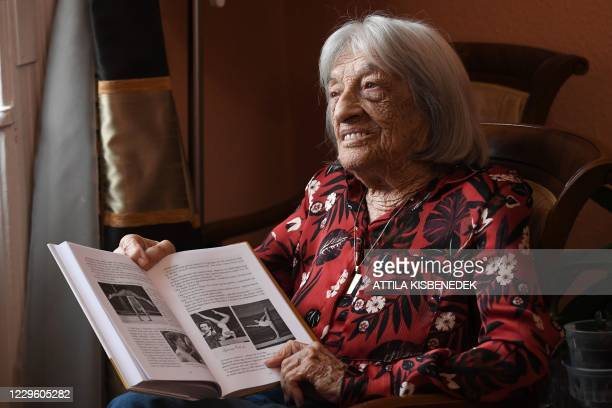 Hungarian-Israeli retired Olympic and world champion artistic gymnast Agnes Keleti shows pictures in her biography in her apartment in Budapest on...