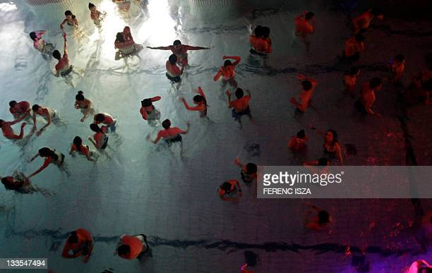 Hungarians and tourists enjoy the music in the pool of the Gellert Thermal Bath during the 'Night of the Baths' event organised by the Budapest...