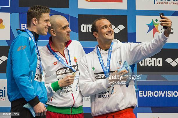 Hungaria's gold medalist Laszlo Cseh Germany's silver medalist Philip Heintz and Portugals bronze medalist Diogo Filip Sjoedin take a selfie as they...