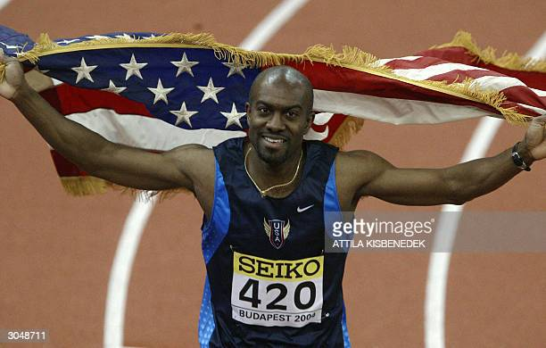 Allen Johnson of the US celebrates with his national flag after winning the final of the men's 60m hurdles in 736sec 06 March 2004 during the 10th...