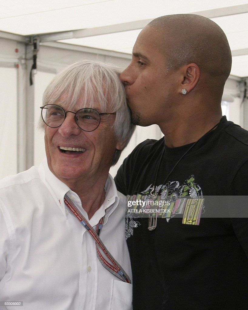 Brazilian soccer champion Roberto Carlos (R) kisses FOM President Bernie Ecclestone in the paddocks of the Hungaroring racetrack before the Hungarish Grand Prix, 31 July 2005 in Budapest, Hungary.