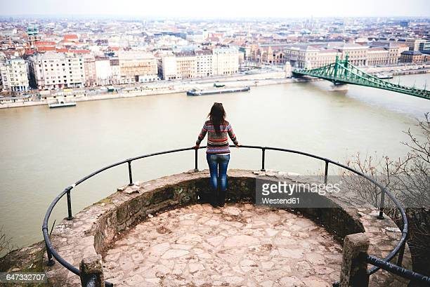 Hungary, Budapest, Woman enjoying the view with Liberty Bridge at Danube river