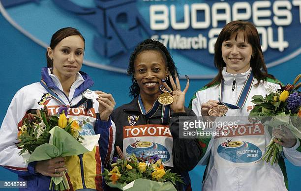 Gold medallist Gail Devers of the US poses with second Kim Gevaert of Belgium and third Belarus Yuliya Nesterenko on the podium of the women's 60m 06...