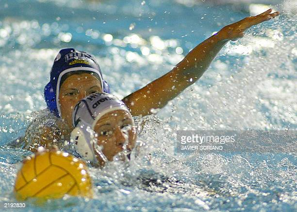 Hungary's Agnes Primasz and Russia's Olga Turova fight for the ball 21 July 2003 in Barcelona during their 10th FINA Water polo World Championships...