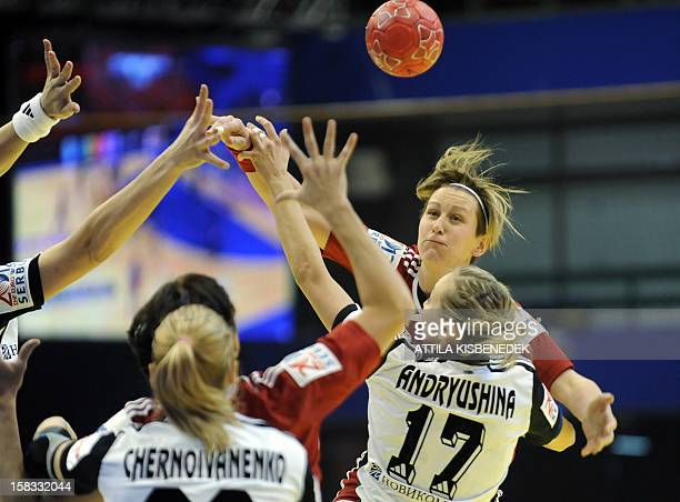 Hungary's Anita Bulath passes the ball between Russia's rightwing Olga Chernoivanenko and Russia's centreback Ekaterina Andryushina during the 2012...