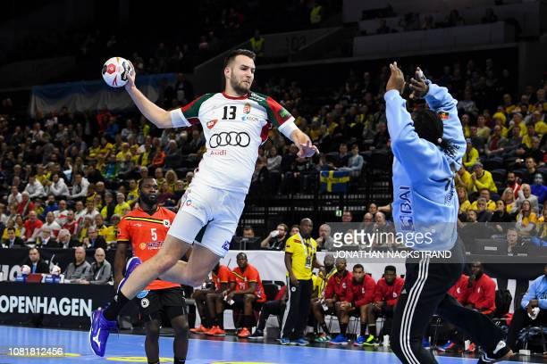 Hungary's Bendeguz Boka prepares to throw the ball to score past Angola's goalkeeper Giovany Muachissengue during the IHF Men's World Championship...