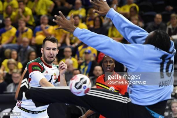 Hungary's Bendeguz Boka scores past Angola's Giovany Muachissengue during the IHF Men's World Championship 2019 Group D handball match between...