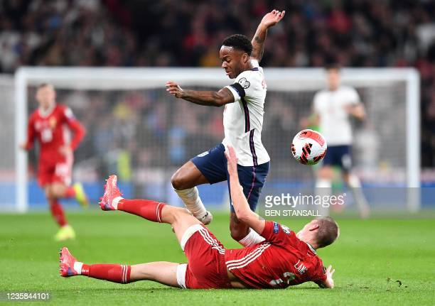 Hungary's defender Adam Lang tackels England's midfielder Raheem Sterling during the FIFA World Cup 2022 qualifying match between England and Hungary...