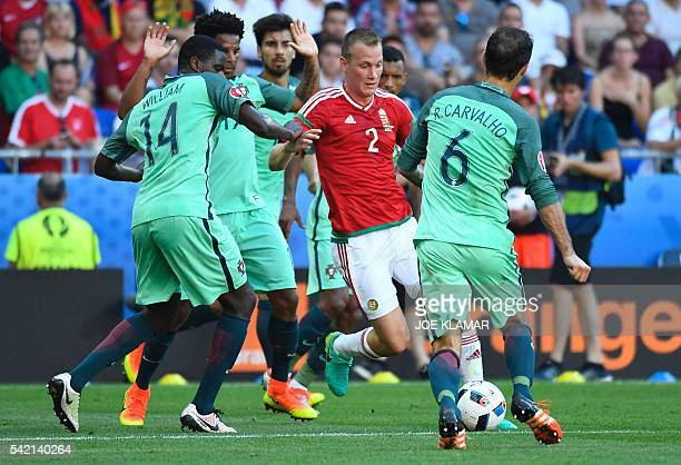 Hungary's defender Adam Lang vies for the ball with Portugal's midfielder William Carvalho and Portugal's defender Ricardo Carvalho during the Euro...