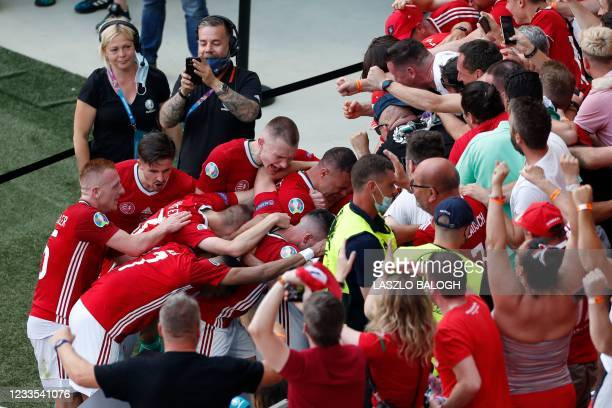 Hungary's defender Attila Fiola celebrates scoring the opening goal with his teammates and fans during the UEFA EURO 2020 Group F football match...