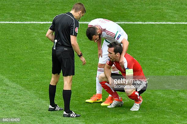 Hungary's defender Attila Fiola checks on Austria's defender Christian Fuchs following a clash during the Euro 2016 group F football match between...