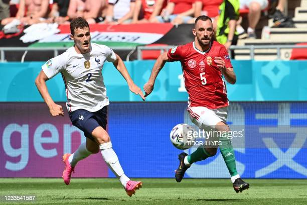 Hungary's defender Attila Fiola gets past France's defender Benjamin Pavard to score the opening goal during the UEFA EURO 2020 Group F football...