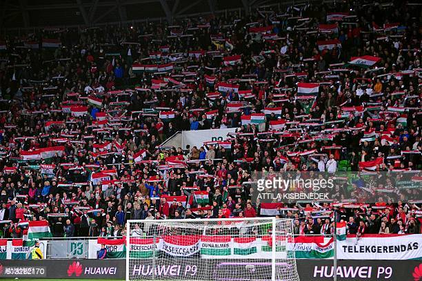 Hungary's fans cheer and wave flags prior to the World Cup 2018 football qualification match between Hungary and Switzerland at the Groupama Arena in...