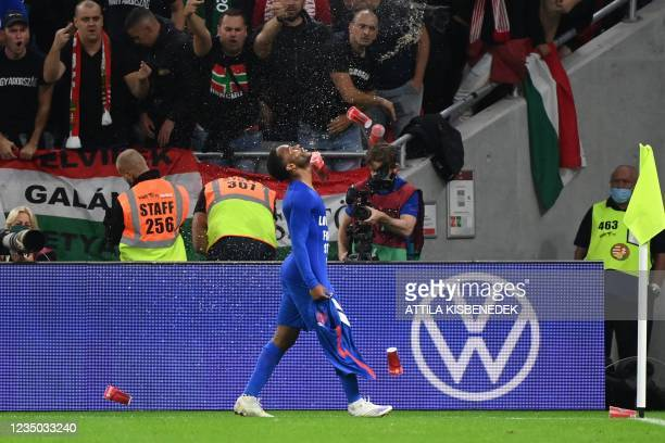 Hungary's fans react throwing cups of beer at England's forward Raheem Sterling as he celebrates scoring the opening goal during the FIFA World Cup...