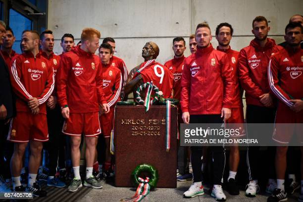 Hungary's football team pay tribute to late Hungarian player and former Benfica player Miklos Feher beside his memorial statue at the Luz stadium in...