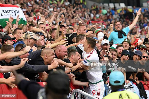 Hungary's forward Adam Szalai celebrates with fans after scoring his team's first goal during the Euro 2016 group F football match between Hungary...
