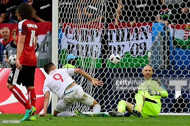 TOPSHOT Hungary's forward Adam Szalai scores a goal despite Austria's goalkeeper Robert Almer during the Euro 2016 group F football match between...