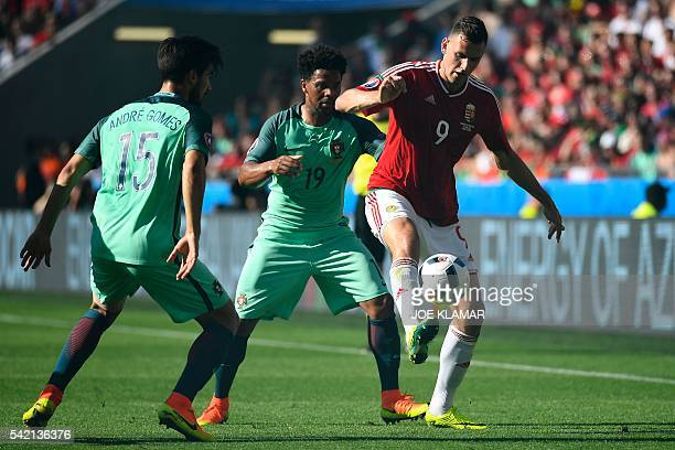 Hungary's forward Adam Szalai vies for the ball with Portugal's defender Eliseu and Portugal's midfielder Andre Gomes during the Euro 2016 group F...